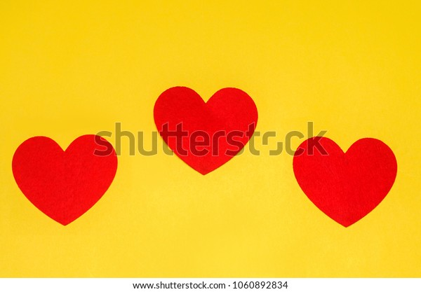 three red hearts on a yellow background, the concept of love, the day of St. Valentine's Day