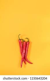 Three red hot chili peppers on yellow surface. Beautiful minimalist food art background. Top view, copy space.