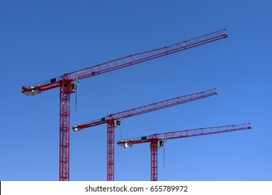 Three red industrial construction tower cranes against blue sky in the background - isolated concept business real estate work erection technology building site progress architecture development