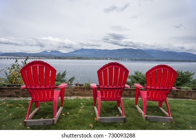 Three red lawn chairs sit in the yard overlooking the lake by Sandpoint, Idaho.