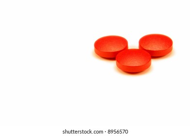 Three red pills isolated on white.