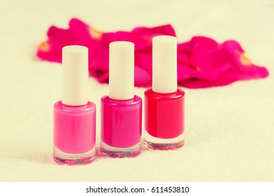 Three red pink bottles of nail polish for manicure decorated with rose petals