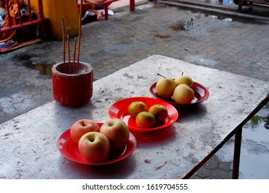 Three red plates of fruits and incense on a table. Used for Chinese prayers