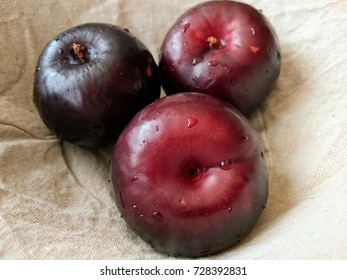 three red and purple plums in linen lined fruit basket