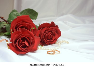 Three red roses on a light background and gold wedding rings.