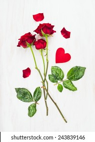 three red roses on long stems and heart on white wood, love card