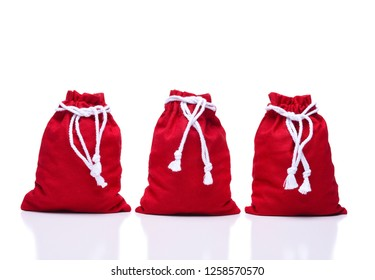 Three red Santa Claus Toy Bags on white. The bags are full and tied closed at the top.