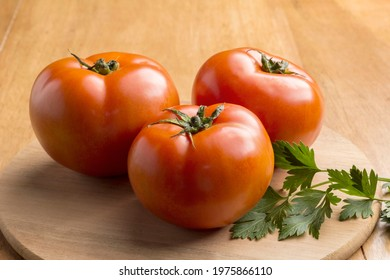 three red tomatoes and parsley on the wood table