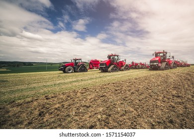 Three red tractors cooperating together within one field during sunny summer day prepared for stubble-tillage after combine harvest.