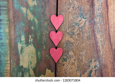 Three red wooden hearts on a colorful table