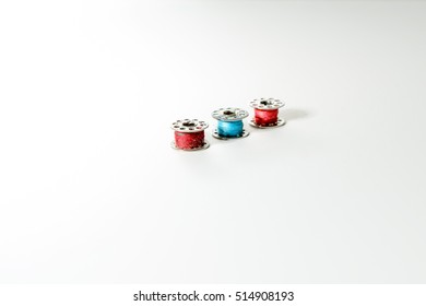 three reels of thread with red and blue sewing thread, isolated on white background