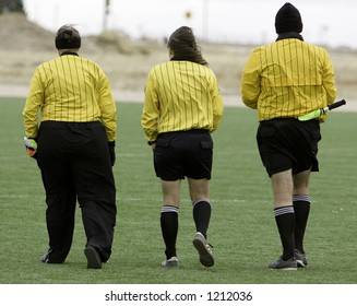 Three referees walking across a soccer field.