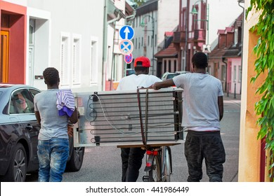 Three refugees black men are transporting refrigerator on Cycling on the road in  the German old town