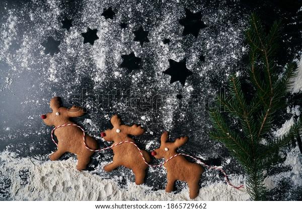 Three reindeer gingerbread cookies on powdered sugar
