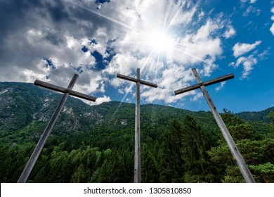 Three religious crosses in mountain with blue sky, clouds and sun rays. Pinzolo, Trentino Alto Adige, Italy