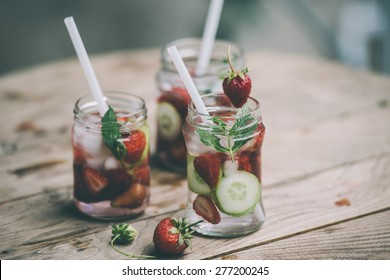 Three retro glass jars of lemonade with  strawberries, cucumber and mint on wooden table. Toned image