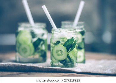 Three retro glass jars of lemonade with cucumber and mint on wooden table. Toned image