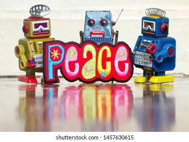 three retro robot toys holding a bright and colorful cloth peace sighn on a old wooden floor with a reflection