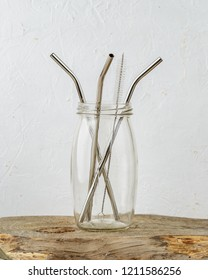 Three reusable metal drinking sraws and cleaning brush in a jar over grey background. Zero Waste and minimalism lifestyle