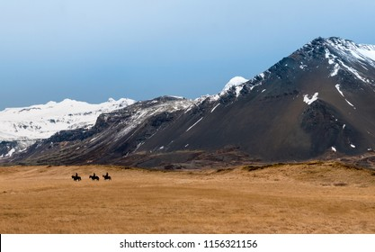 Three riders and their horses along the Icelandic landscape with mountain backdrop, Iceland