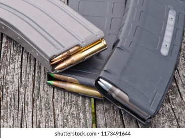 Three rifle magazines containing different types of .223 caliber bullets together with a wooden background