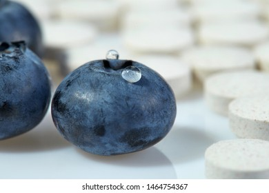Three ripe blueberries on a background of tablets spread out on a light surface. Concept: natural vitamins. Close up.