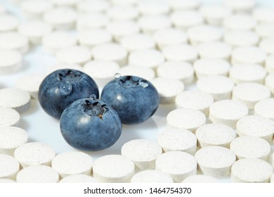 Three ripe blueberries are surrounded by pills on all sides. Concept: natural vitamins.