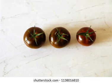 Three ripe and delicious black cherry tomatoes on the kitchen table