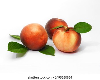Three ripe peaches with leaves. White background.
