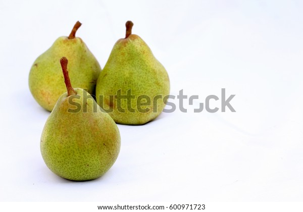 three ripe pears on white fabric with copy space, simple fruit composition