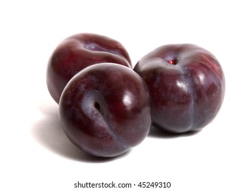 three ripe plums isolated on white