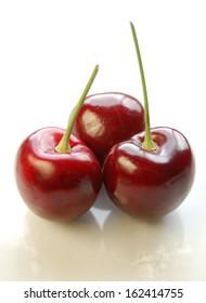 Three ripe red cherries on white marble.