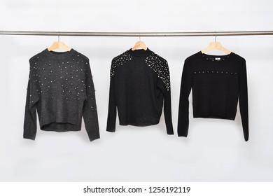 Three rivets black sweater on hanger