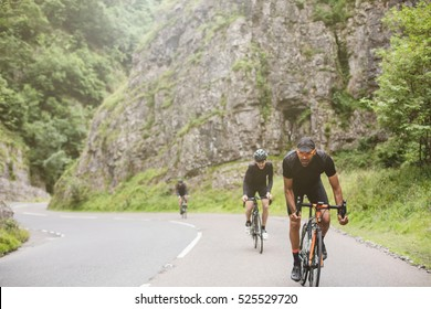 Three road cyclists attacking the climb in Cheddar Gorge