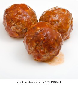three roasted meatballs under meat sauce on white plate