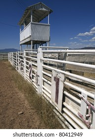 Three rodeo gates beneath the announcer's booth at a rural rodeo.