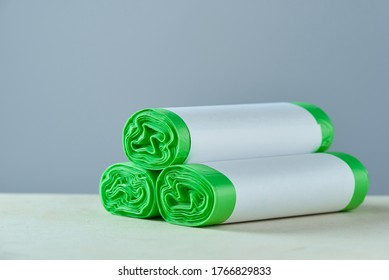 Three roll green eco garbage bag with copy space isolated on grey background.