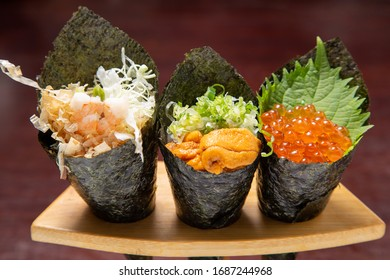 three rolls of Japanese seaweed roll sushi, shrimp, urchin and salmon egg roll with seaweed on roll stand.