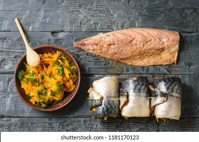 Three rolls of mackerel with vegetables, a bowl of vegetables and sliced fish carcass on a wooden table. The view from the top. Flat lay.