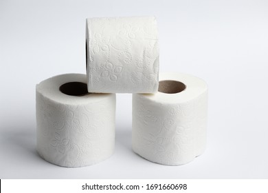 Three rolls of toilet paper on a light background