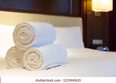 Three rolls of white bath towel on hotel bed