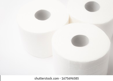 Three rolls of white bathroom toilet paper on a white dreamlike background, horizontal landscape orientation shot from above with high-key lighting.