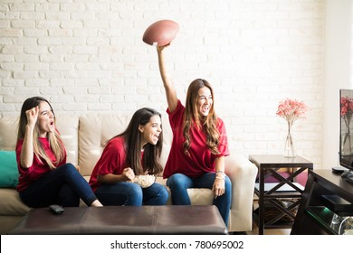 Three roomies wearing team jerseys and watching a football team on tv, celebrating a touchdown