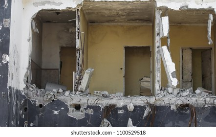 three rooms of a completely destroyed house with collapsed walls and rubble