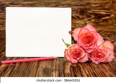 Three roses with blank greeting card and pink pencil on a wooden background