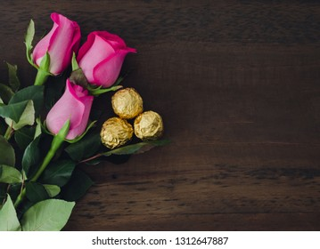 Three roses with chocolates on wooden background. Space to copy. Top view.