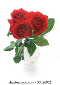 Three roses of red color in a white vase.