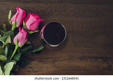 Three roses and wine glass on dark wooden background. Space to copy. Top view....