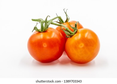Three round red tomatoes with green branch on white background