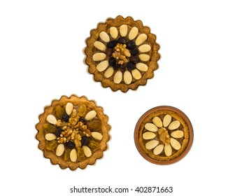 """Three round traditional Polish Easter cakes """"Mazurek"""" with almonds, raisins and walnuts on the white background"""